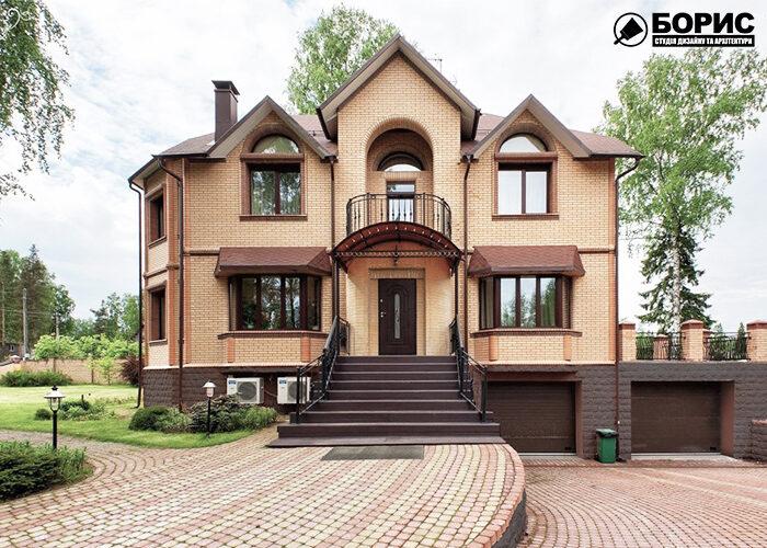 Великий будинок з цегли з гаражем виконаний в класичному стилі.