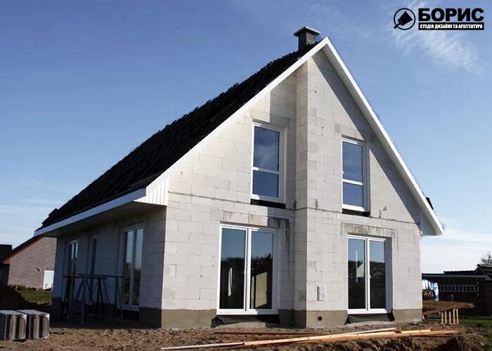 Строительство дома из газобетона с покатой крышей и большими окнами.